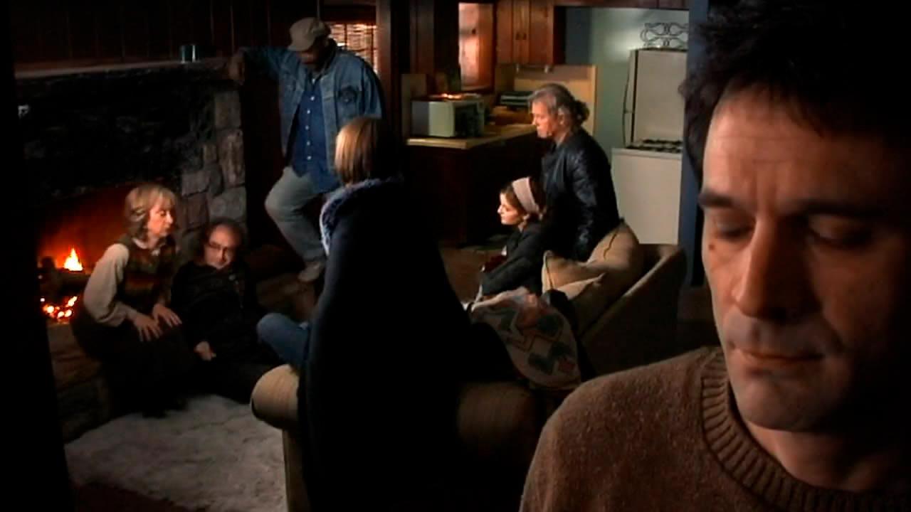 Escena representativa de The man from Earth: el salón de la casa, y los amigos charlando.